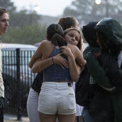 Friends of Sincere Ash embrace in the rain.   Colin Boyle/Sun-Times