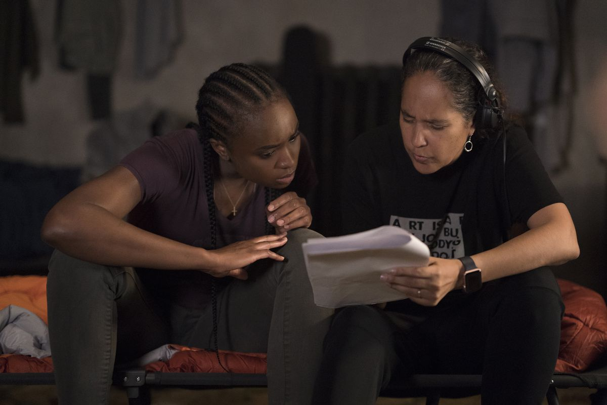 Director Gina Prince-Bythewood and star Kiki Layne go over a script page on the set of The Old Guard.