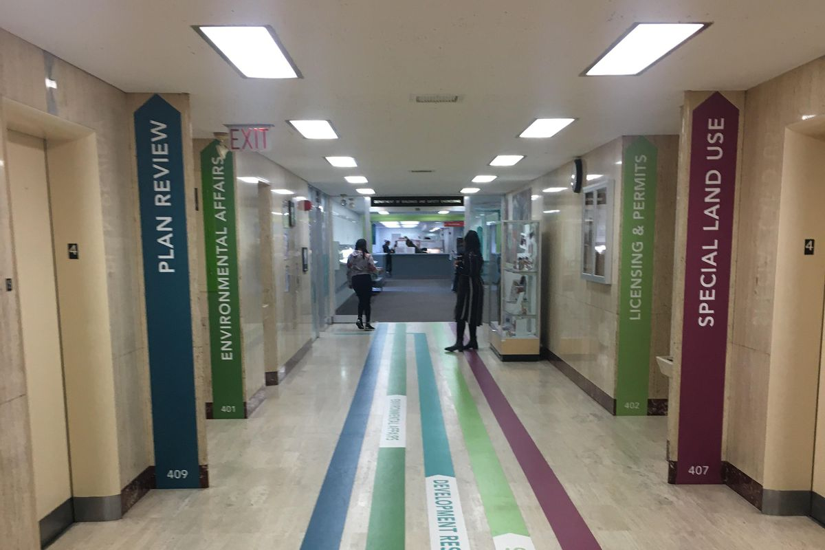 A hallway with colored lines painted on the floor. Colors match signs on the walls.