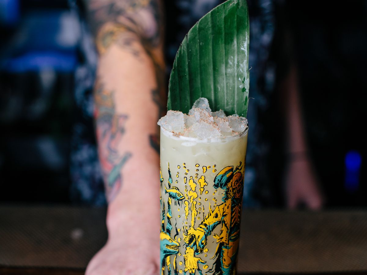 A white tattooed bartender pushes a tiki cocktail with a big green leaf towards the camera.