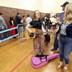 """Lottie Johnson, Deseret News arts and entertainment assistant editor, plays guitar while waiting for """"American Idol"""" auditions at the Northwest Community Center in Salt Lake City on Thursday, Aug. 29, 2019."""