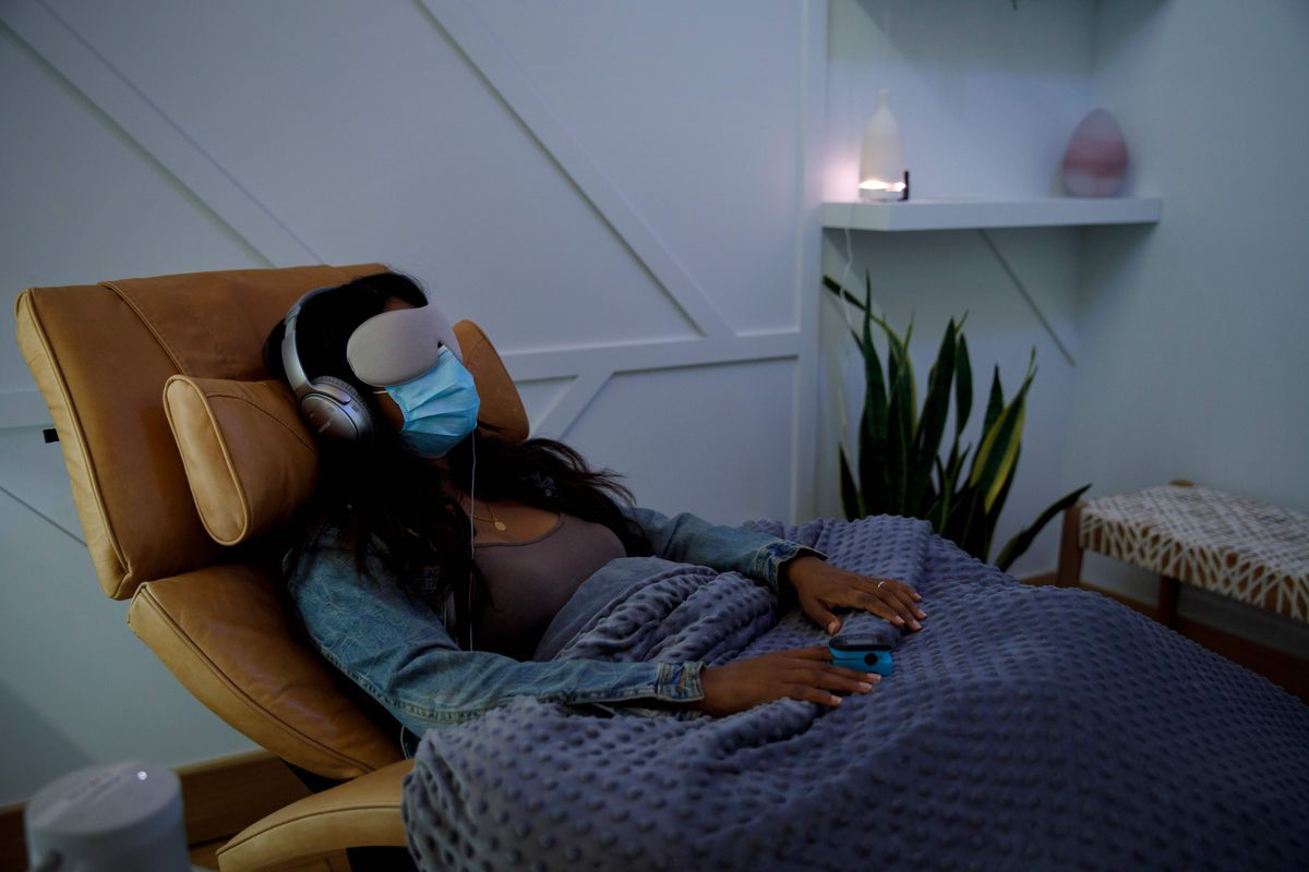A person wearing an eye mask, breathing mask, headphones, and lap blanket sits in a comfortable chair.