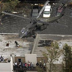 Residents wait on the roof of an apartment complex Thursday to be evacuated from the floodwaters of New Orleans after Hurricane Katrina.