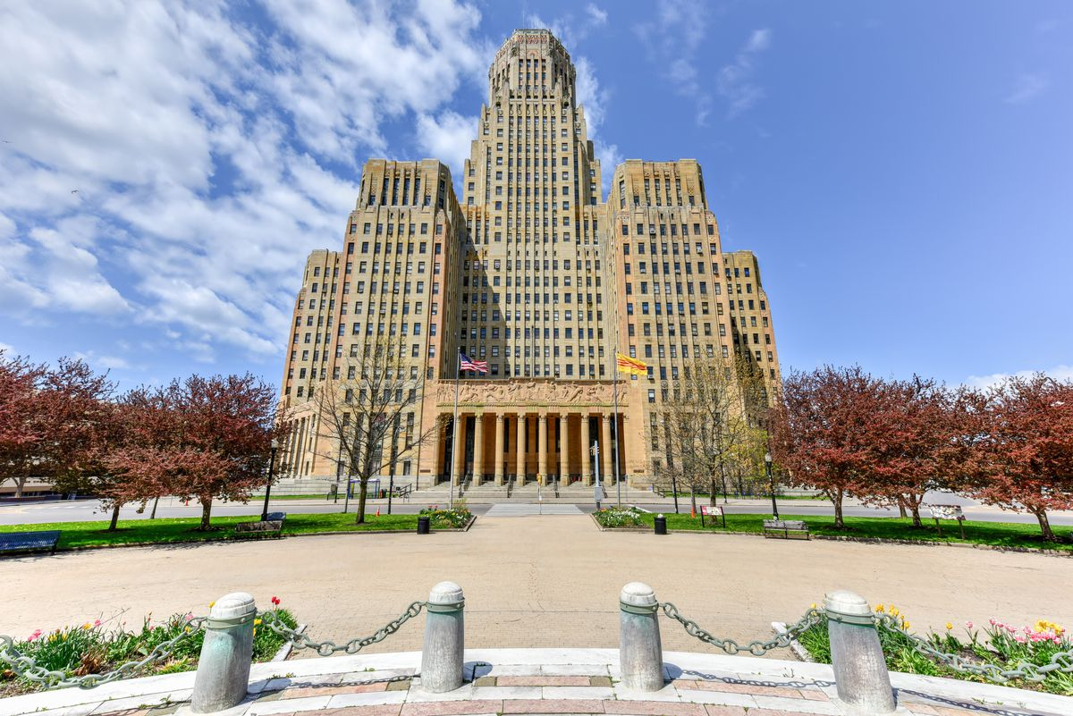 The exterior of Buffalo City Hall. The building is tan. There is a courtyard with trees in the foreground.