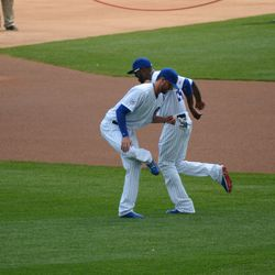 1:00 p.m. Kris Bryant stretching, with Dexter Fowler running by -
