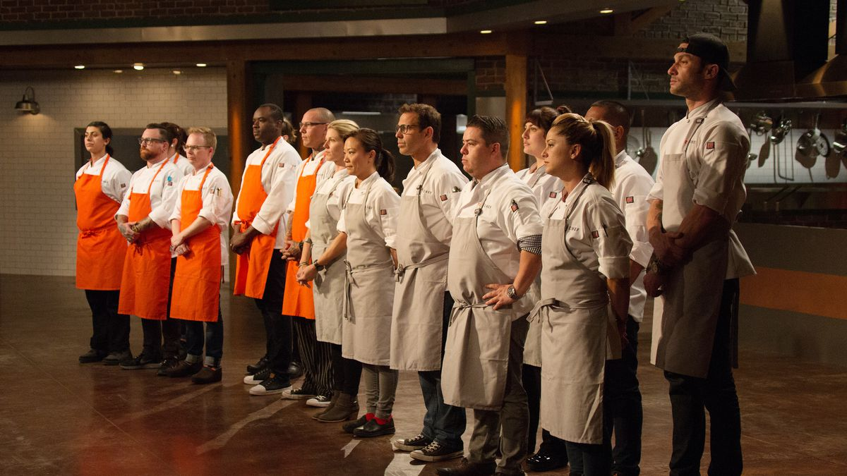 A group of chefs — half in orange aprons and the other half in tan ones — look off to the left while on the reality show 'Top Chef.'