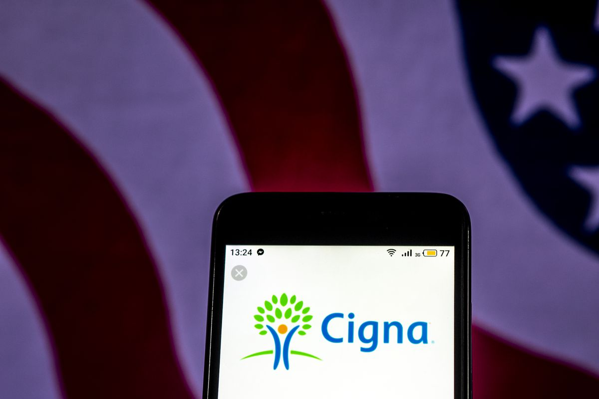 A mobile phone showing the Cigna health care app, in front of an American flag.