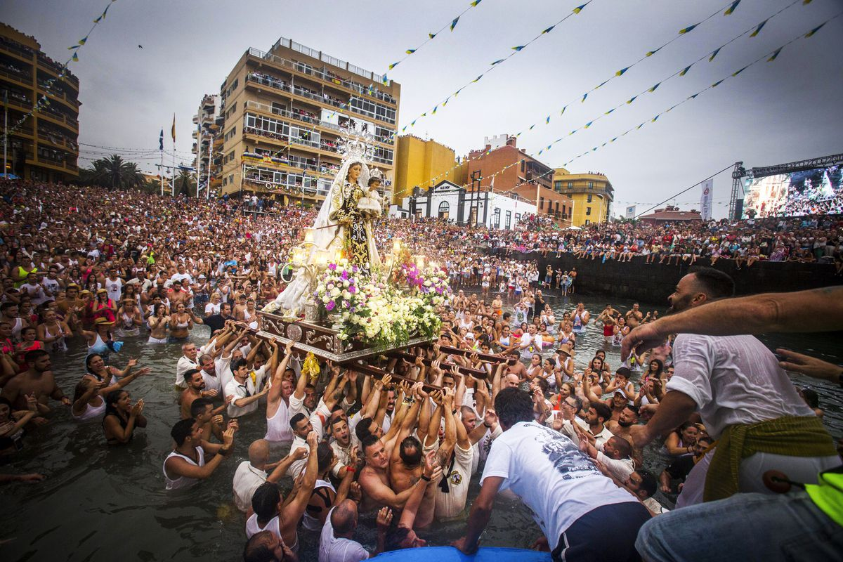 July 10: Every year, local residents of the Spanish Canary Island of Tenerife carry the statue of the Virgin del Carmen, patron saint of fishermen, from its chapel to a small beach in the fishing habor. Once at the beach, the fishermen put the statue on b