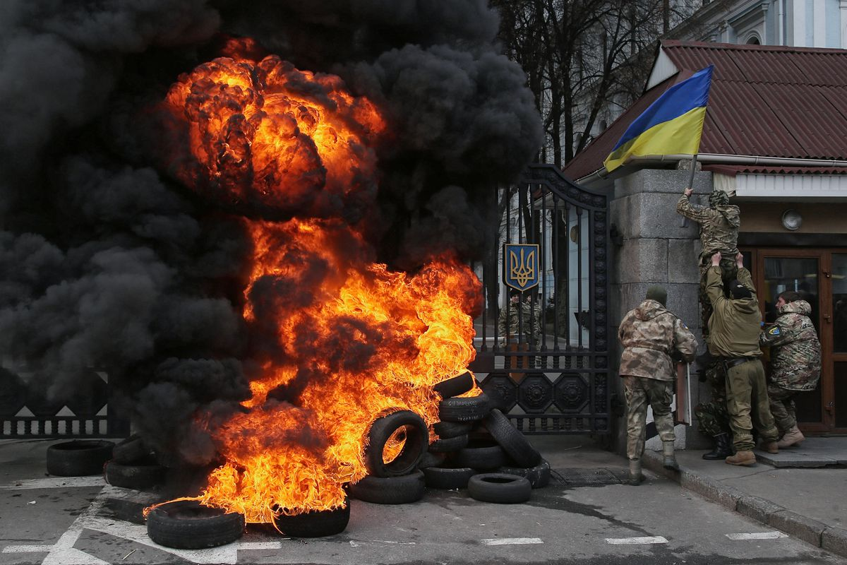 Soldiers from Ukraine's Aydar battalion, which has been accused of serious human rights abuses, burn tires in front of Ukraine's Ministry of Defense to protest a rumored plan to disband the battalion