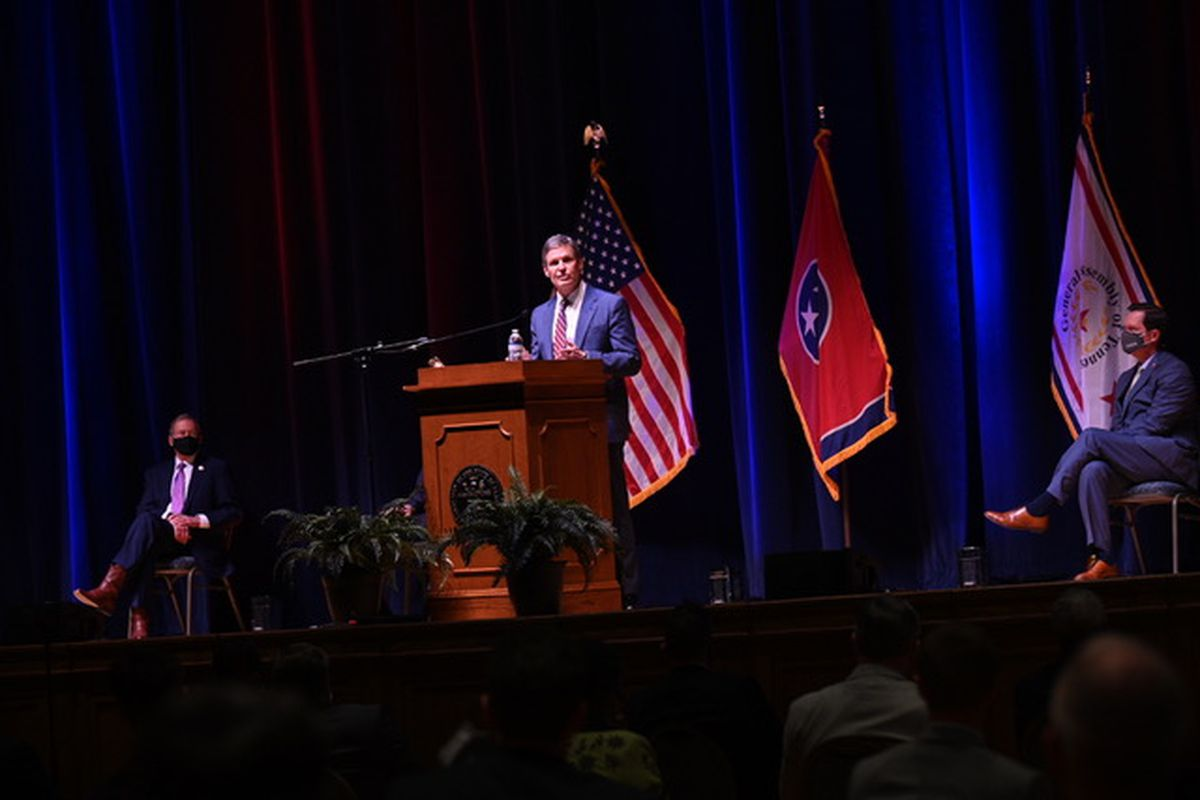 Gov. Bill Lee stands on stage behind a podium in front of an American and Tennessee flag. State legislators are spaced out in the audience to social distance.