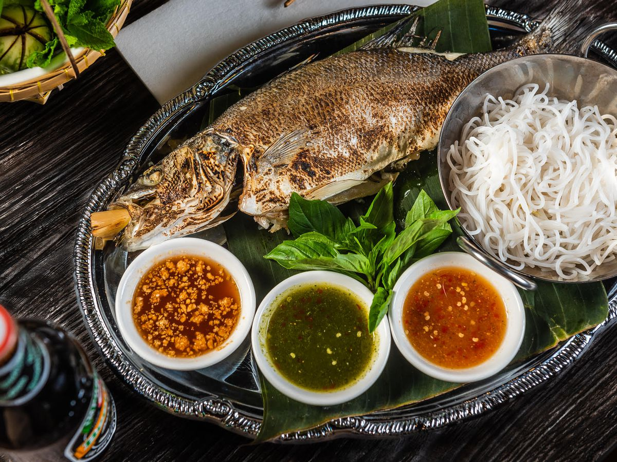 A whole grille dfish with three dipping sauces, herb garnishes and vermicelli noodles on an intricate blue plate