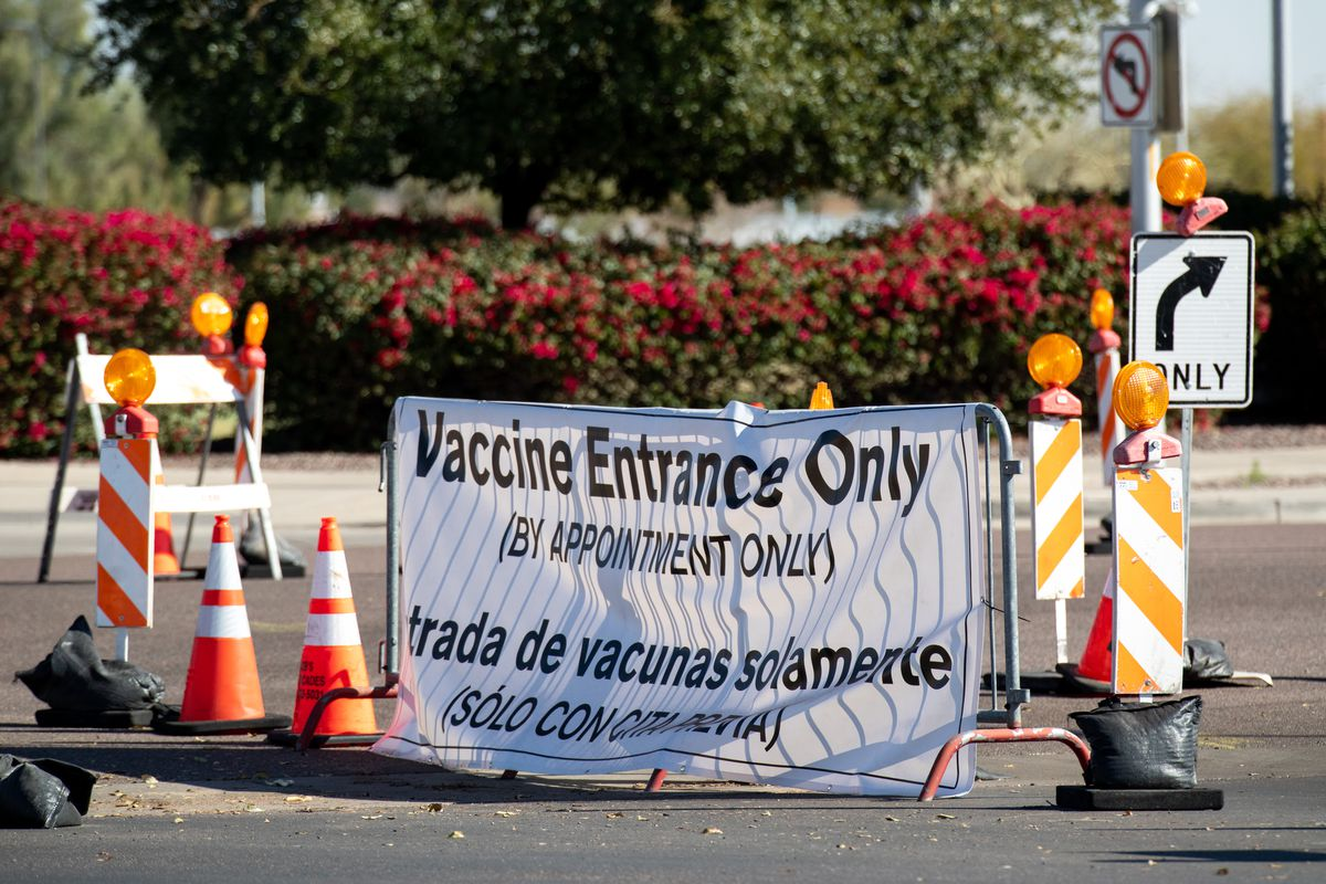 "A sign on a street barricade reads ""Vaccine entrance only, by appointment only"" in English and in Spanish."