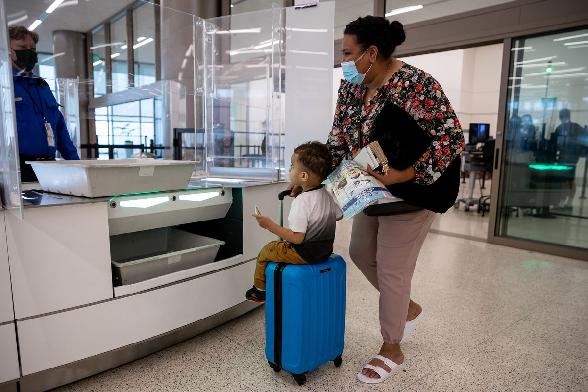 Pasepa Kolo wheels her suitcase with her nephew, Alamoni Filimoehala, 1, sitting on top at the security screening checkpoint at Salt Lake City International Airport in Salt Lake City on Wednesday, Aug. 18, 2021.