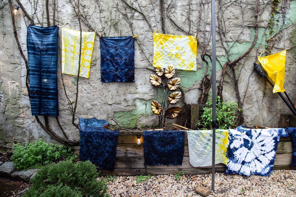 an outside wall with string hanging blue and yellow tie-dyed pillowcases and t-shirts