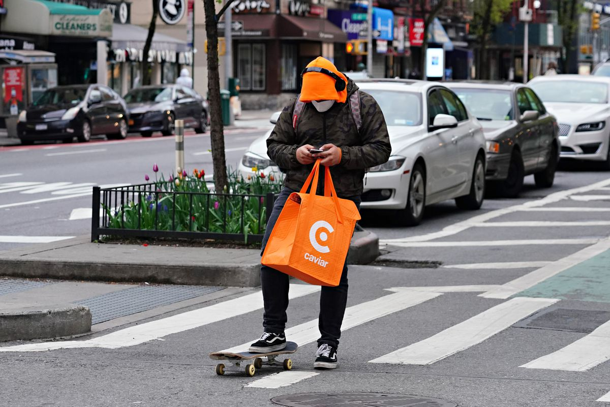 Man carrying a Caviar bag and wearing a mask looks down at his phone in the middle of a crosswalk.