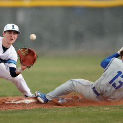 Layton's Austin Tidwell, left, waits for the ball as Bingham's Kason Brooksby slides safe into second base as they play a baseball game in Layton on Tuesday, March 23, 2021.