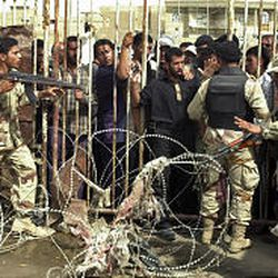 Members of the Iraqi National Guard try to control men lining up to surrender their weapons in Baghdad.