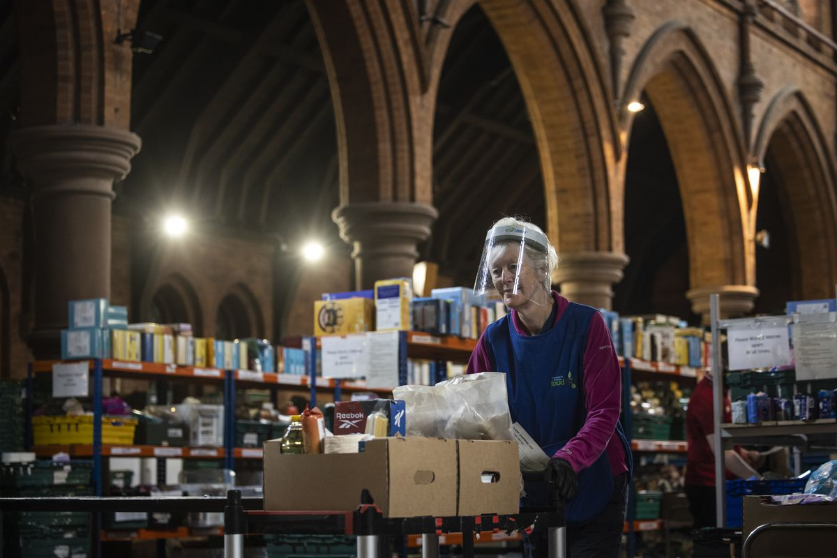 A worker in a visor pushes a trolley of food parcels inside a food bank church filled with surplus food