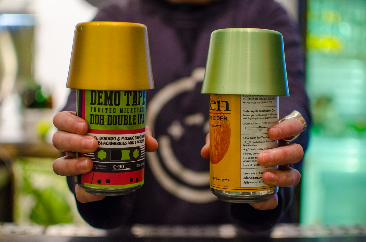 Two hands hold out beer cans, each covered with an upside-down colorful aluminum cup