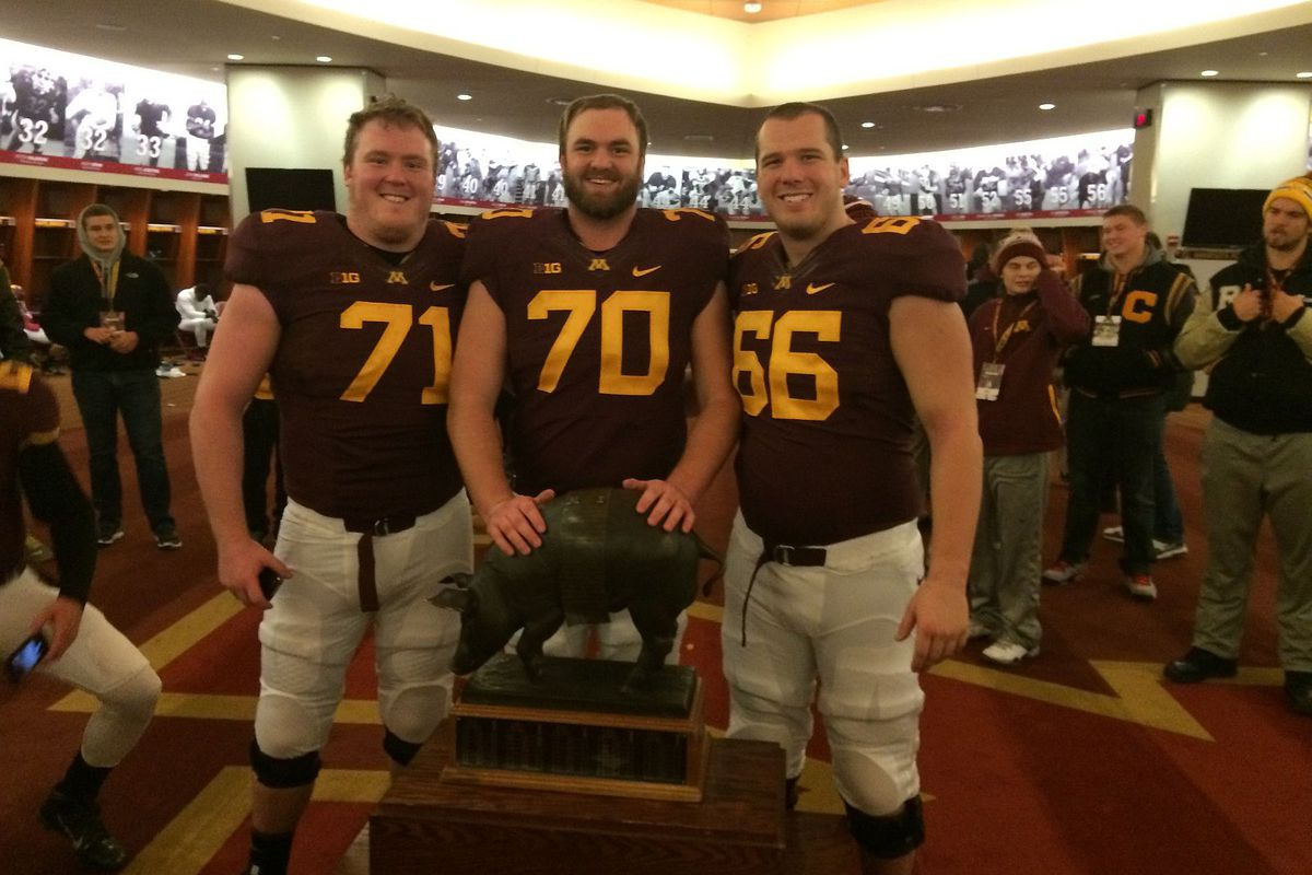 Luke McAvoy, far right, with fellow Minnesota teammates and the Floyd of Rosedale trophy after beating Iowa.