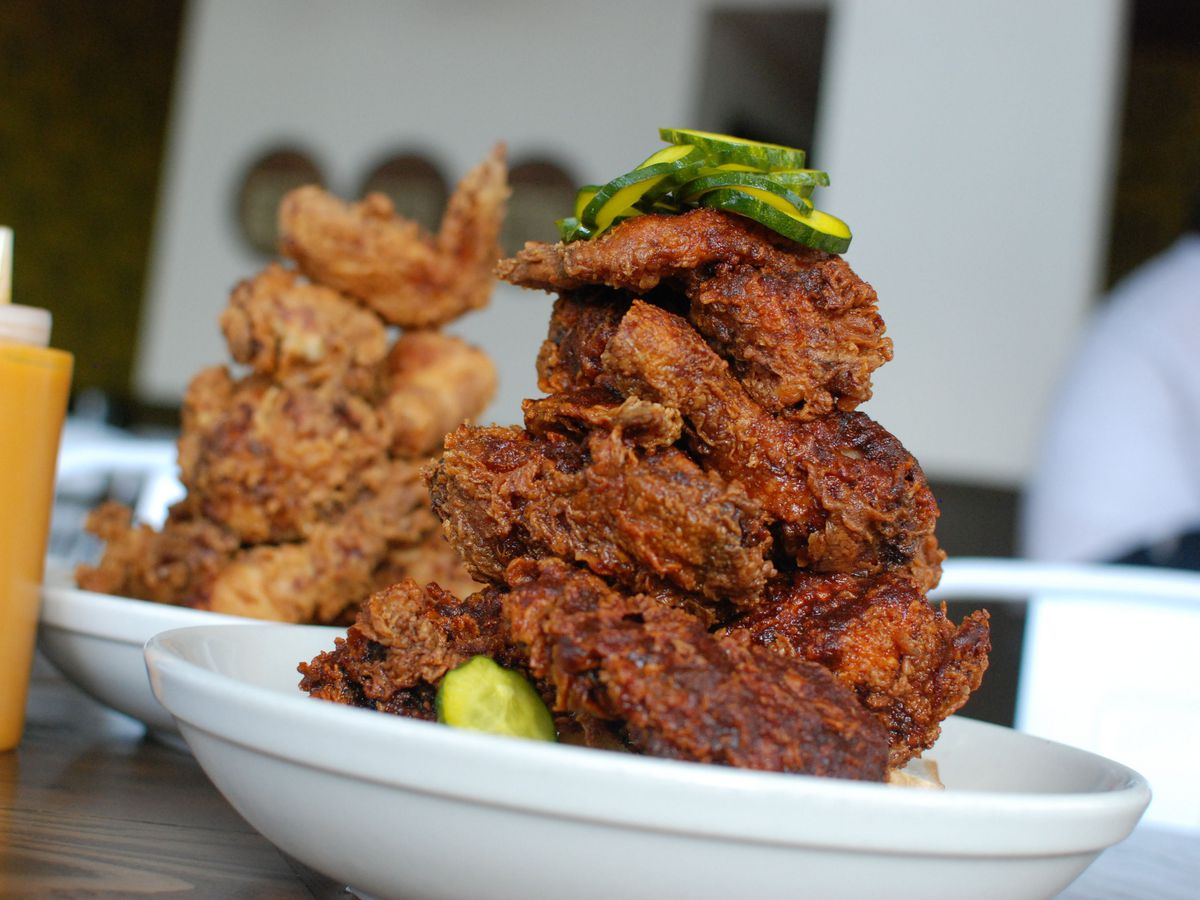 Two towering plates of fried chicken, one bright orange with Tennessee Hot seasoning