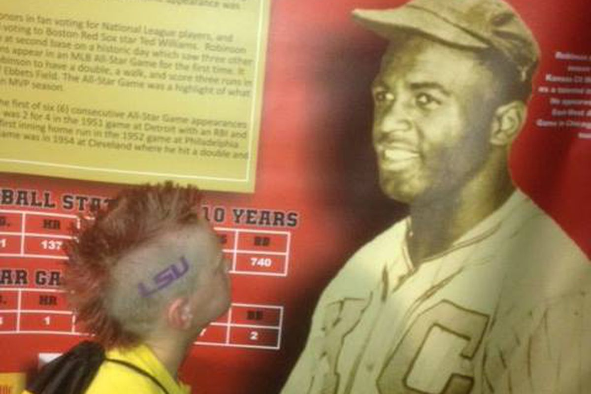An LSU fan visits the Negro Leagues Baseball Museum exhibit and stares into Jackie Robinson's eyes.