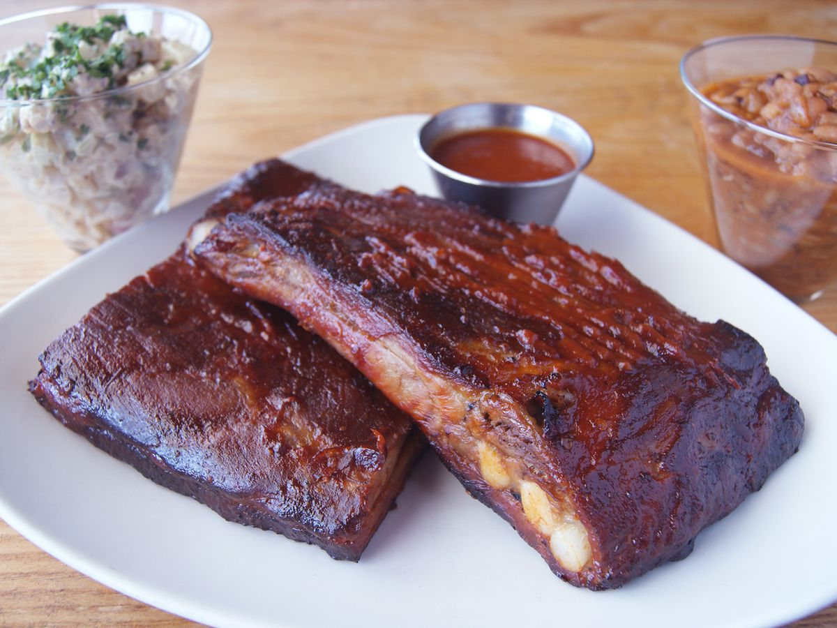 A half rack of ribs with barbecue sauce and beans on the side