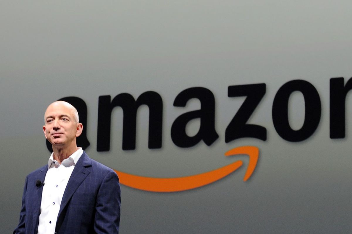 Amazon CEO Jeff Bezos standing in front of the Amazon smiling sign