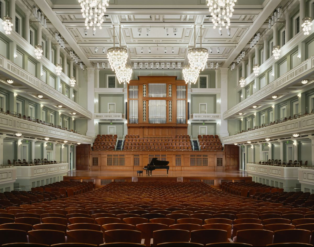 The interior of the Schermerhorn Symphony Center in Tennessee. The walls and ceiling are white. The stage and seats are wood. There is a grand piano on the stage.