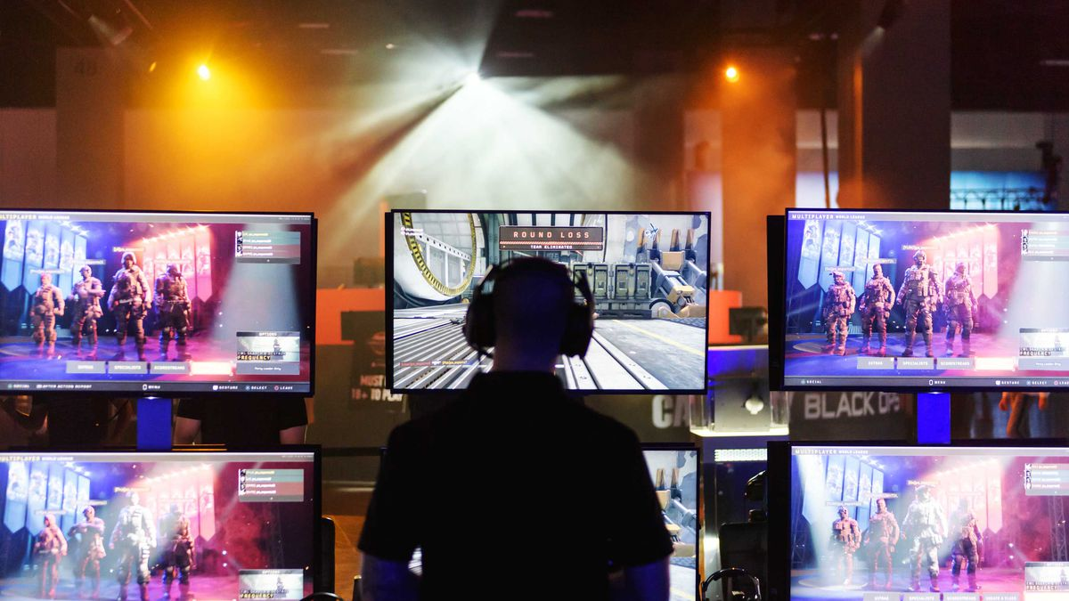 A man is surrounded by six screens showing the video game Call of Duty.