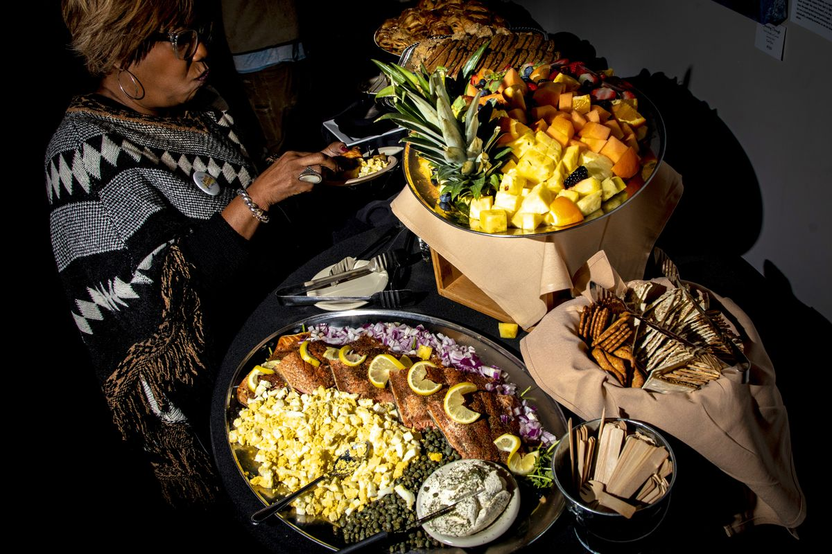 A woman next to a large spread of food including smoked salmon and fresh fruit.