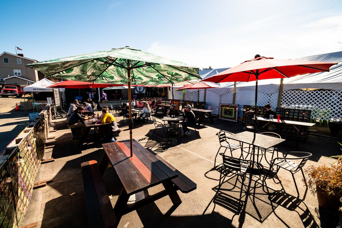 An outdoor beer garden in a parking lot is embellished with picnic tables and umbrellas