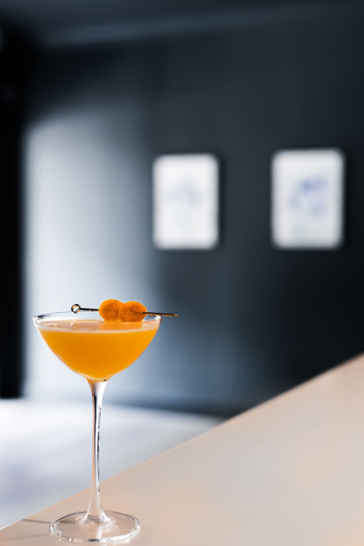 An orange cocktail in a rounded martini glass with a skewer of garnish.