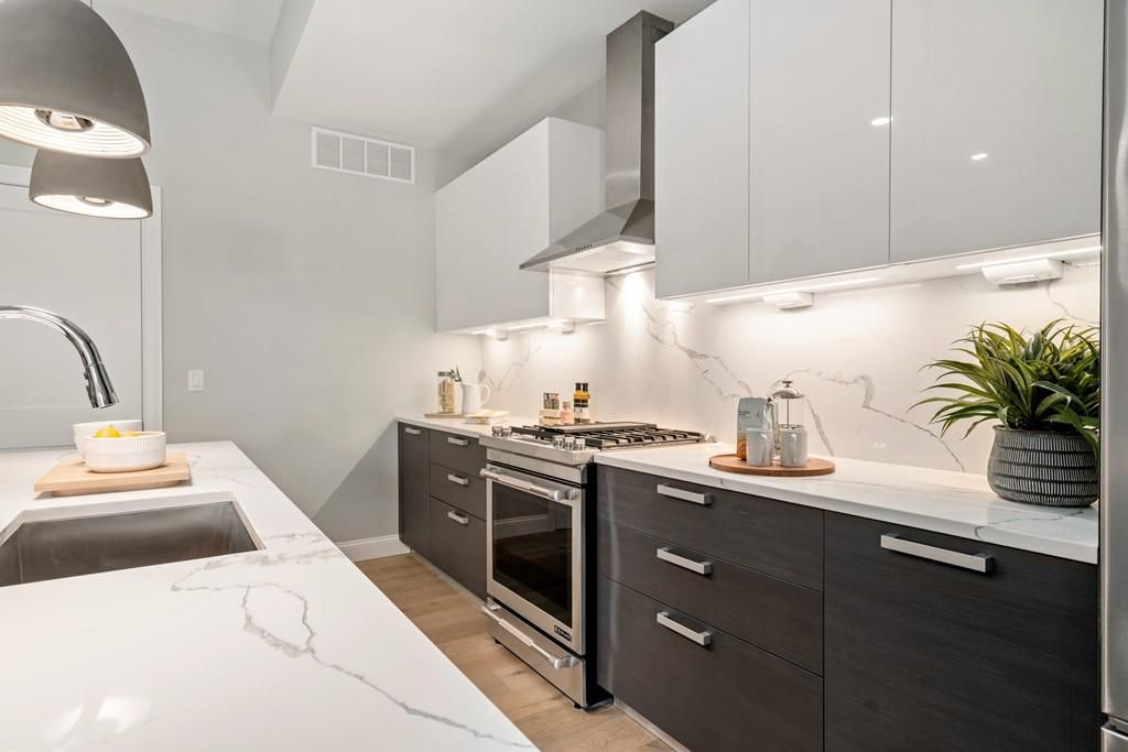 A modern kitchen with a long counter and an island with a sink in it.