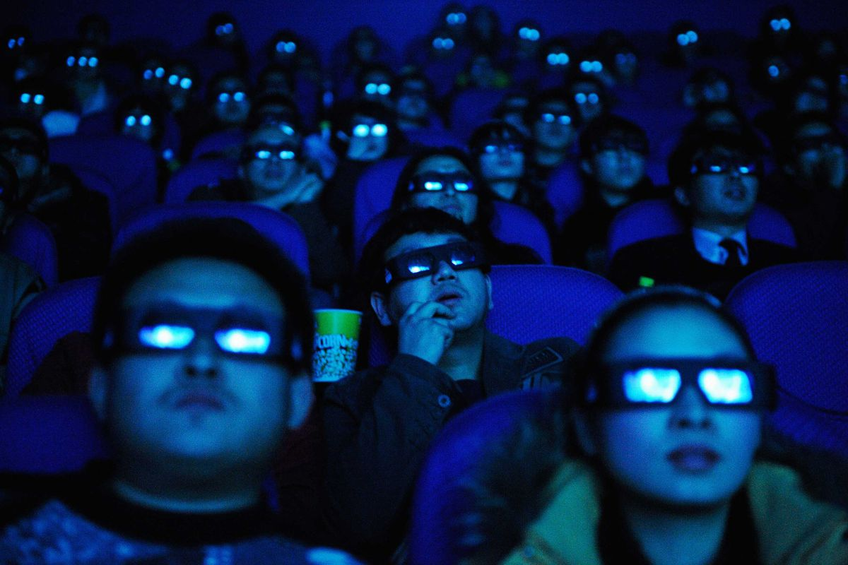 Moviegoers wearing 3-d glasses watch Avatar in a dark movie theater.