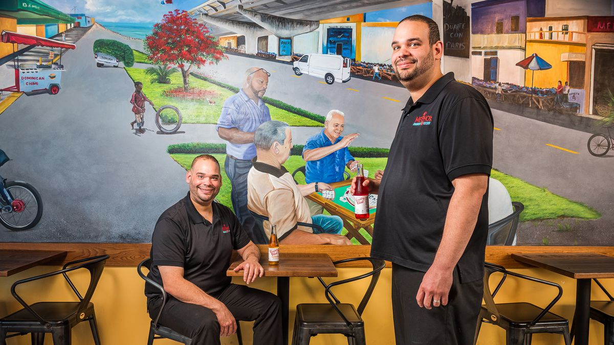 Twin brothers Aris and Raymond Compres stand in front of a mural at Mecho's that depicts regulars at their other Dominican restaurant in D.C.