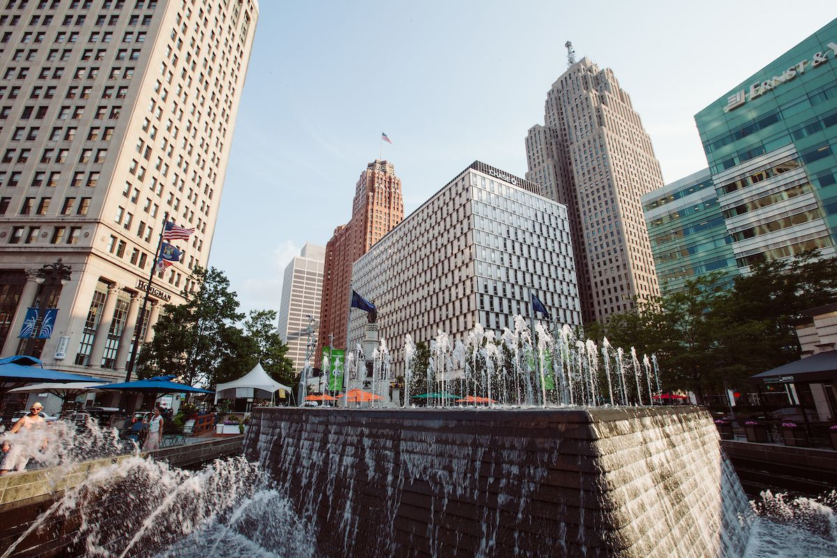 In the foreground is a large fountain. In the distance are various tall city buildings.