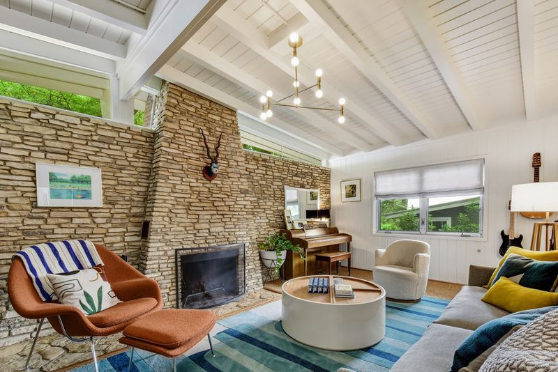 A living room has a large stone fireplace, red chair, blue rug, and a chandelier.