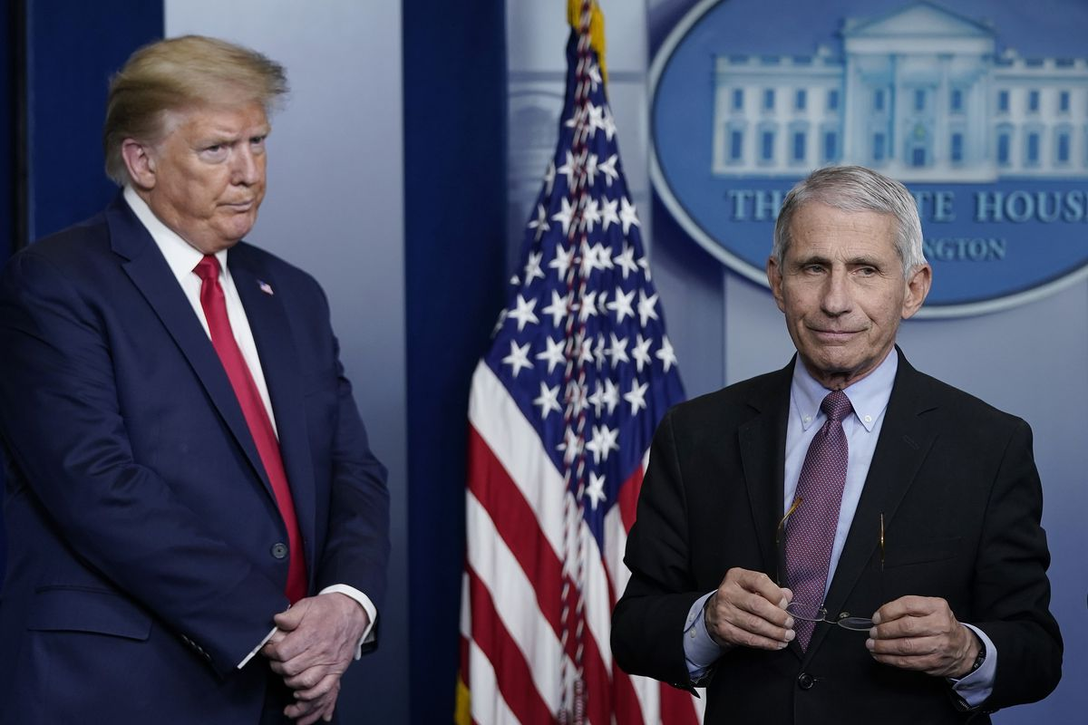 Fauci, right, holds his glasses and listens to a question, as Trump looks on with a serious expression.