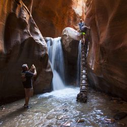 A man takes a photo of the Kanarraville Falls, on  June 6, 2017 near Kanarraville, Utah.  What used to be a treasure has now become a nightmare for many Kanarraville residents. The influx of hikers has left the small community of 350 faced with many difficulties they would have never known otherwise, including parking problems and fears of contamination of the primary water source.  (Jordan Allred /The Spectrum via AP)