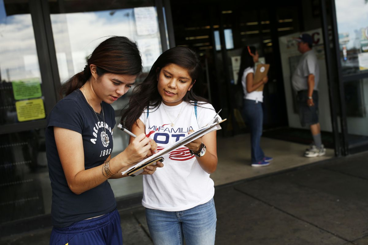 In this June 9, 2016 photo, Fabiola Vejar, right, registers Stephanie Cardenas to vote in front of a Latino supermarket in Las Vegas. Shielded from deportation under an Obama administration program that protects those brought to the country illegally as c