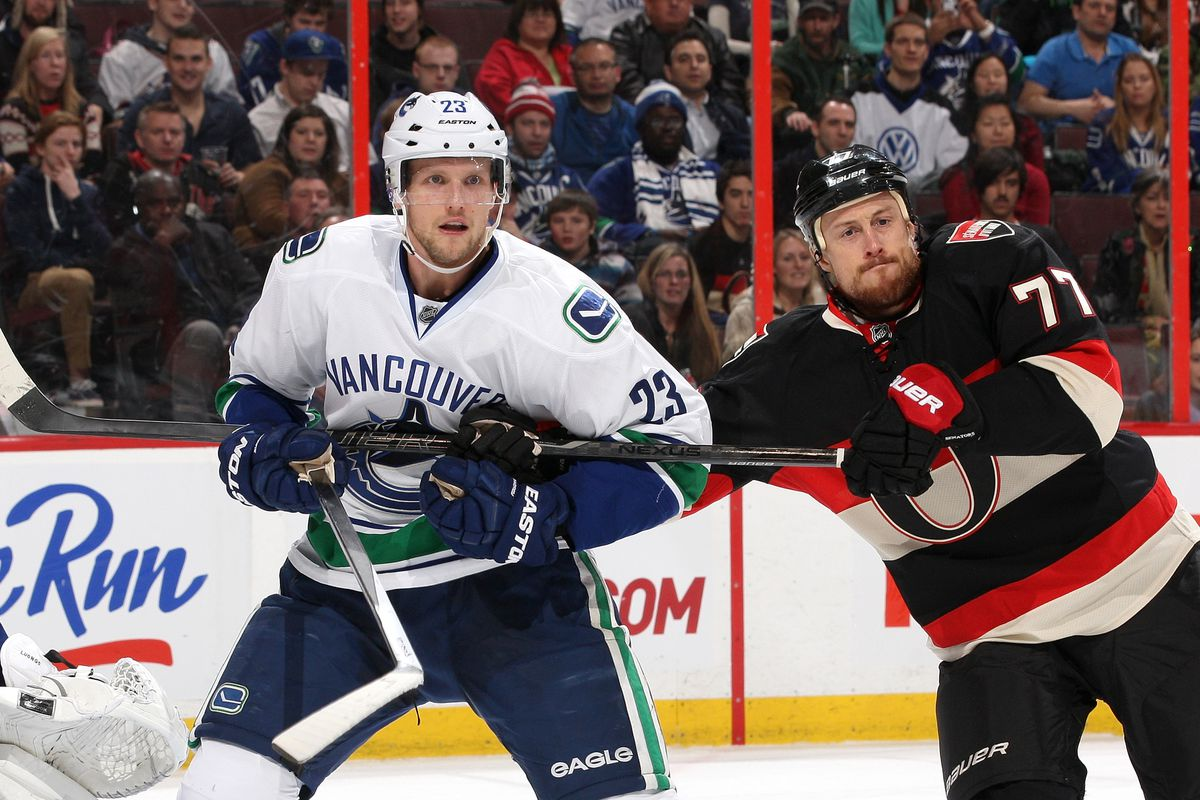 Alex Edler tries not to stare at the terrifying little head growing out of Joe Corvo's left shoulder.