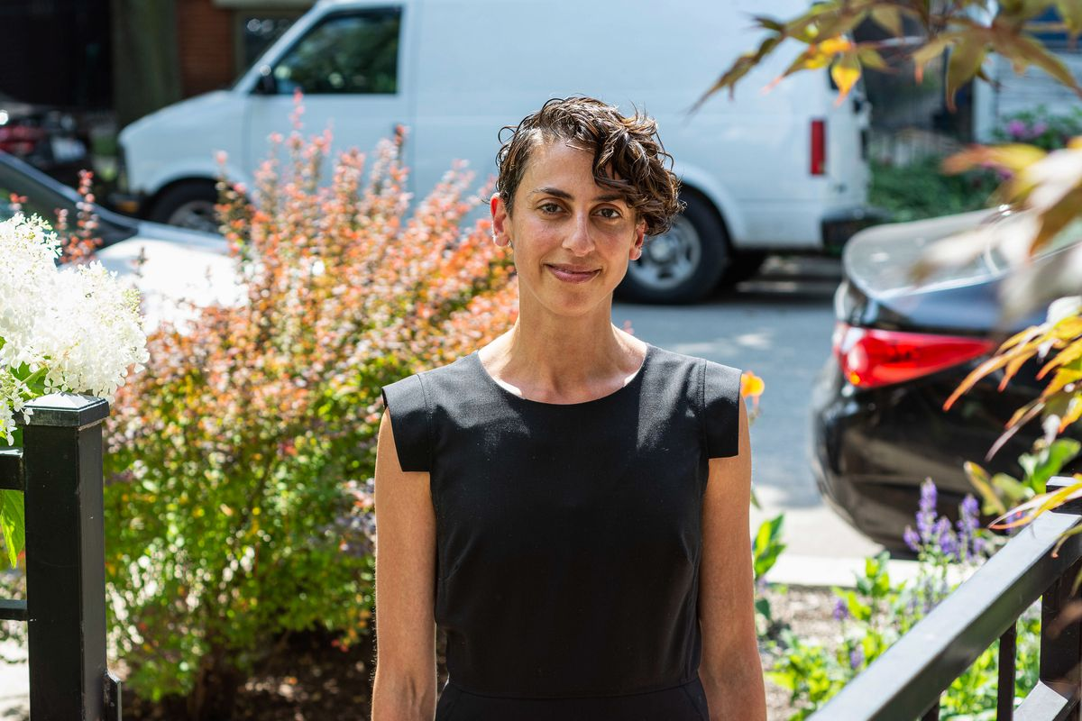 Rachel Shapiro poses on a sunny day outside of her Chicago home, cars lining the street behind her.