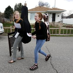Vivian Stewart, 13, and her mother, Kelly McConkie Stewart, return to their car after performing for Helen Gygi in Salt Lake City on Wednesday, April 1, 2020. The mother/daughter duo have been performing concerts to not only lift their neighbors' spirits, but their own as well.