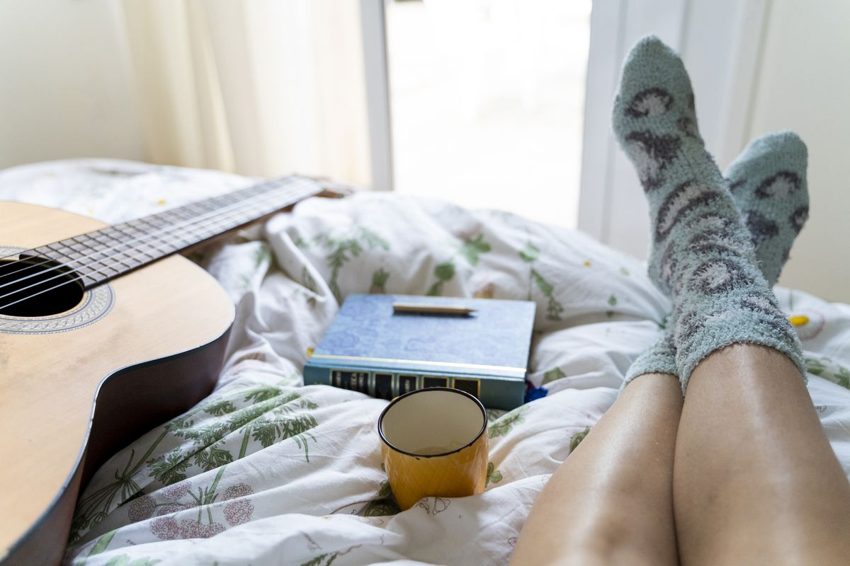 Image of a person in bed, showing their feet, a guitar, a mug, and a book.
