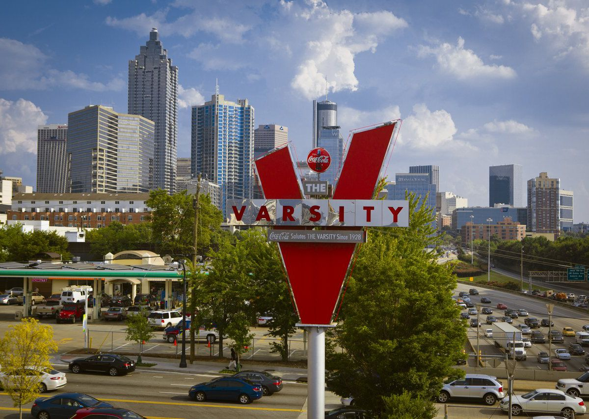 """Large red and white V-shaped sign with """"Varsity"""" on it."""