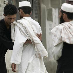 In this Friday, Sept. 7, 2012 photo, Pakistani security men search a worshiper before he can enter the Shiite mosque Imam Bargah Kallah in Pakistan's violent Baluchistan capital of Quetta, Pakistan, where radical Sunni Muslim rivals have terrorized and murdered minority Shiites in a wave of suicide bombings and target killings. In recent years Pakistan's sparsely populated southwestern Baluchistan province has been spiraling deeper into chaos, wracked by a secessionist insurgency that has been overtaken in the last two years by a violent sectarian campaign.