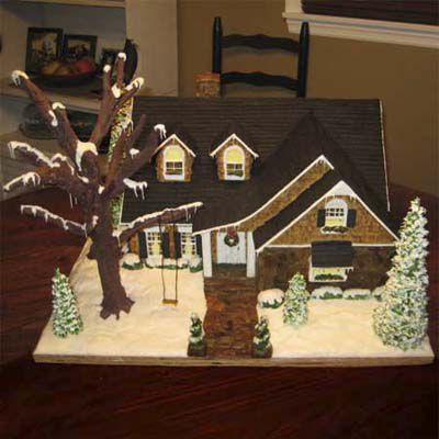 Gingerbread cottage with tree and swing outside.