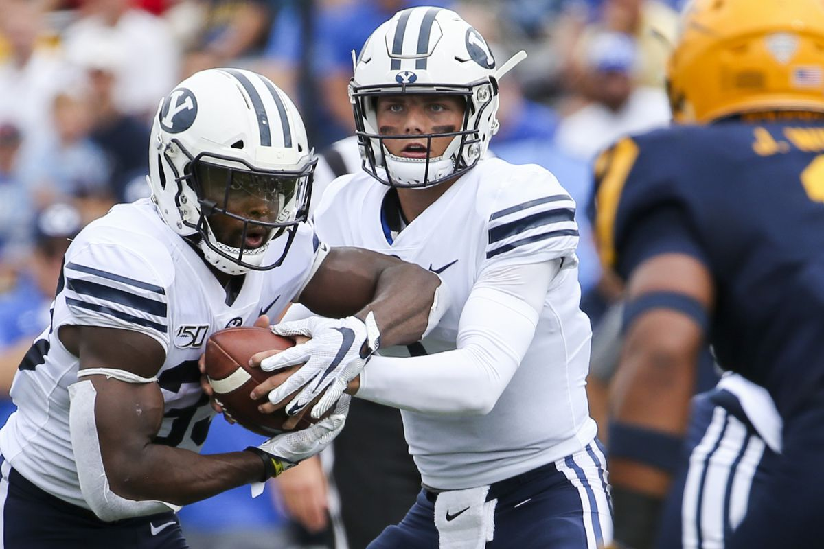 Brigham Young Cougars quarterback Zach Wilson (1) fakes a handoff to Brigham Young Cougars running back Emmanuel Esukpa (33) during the first half of an NCAA football game at The Glass Bowl in Toledo, Ohio on Saturday, Sept. 28, 2019.