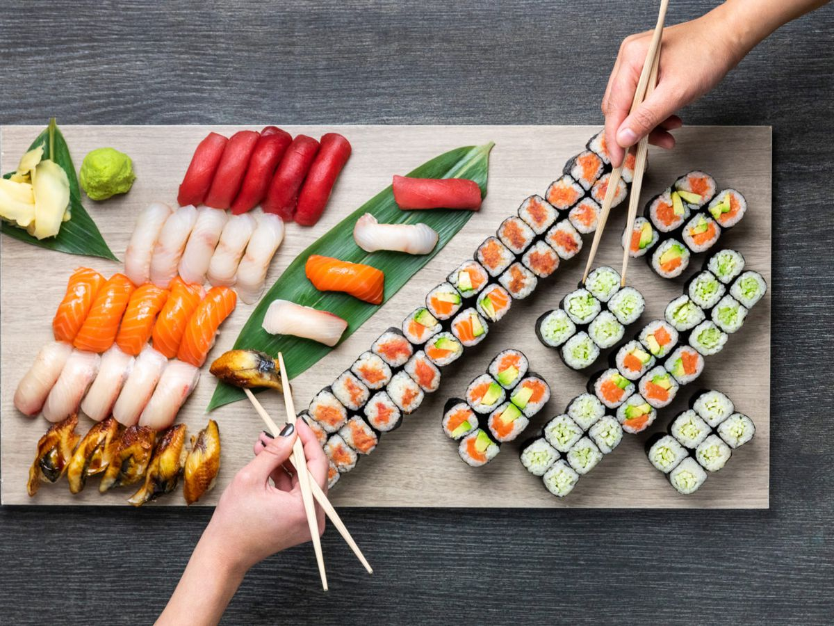 A variety of sushi, with two hands sharing using chopsticks